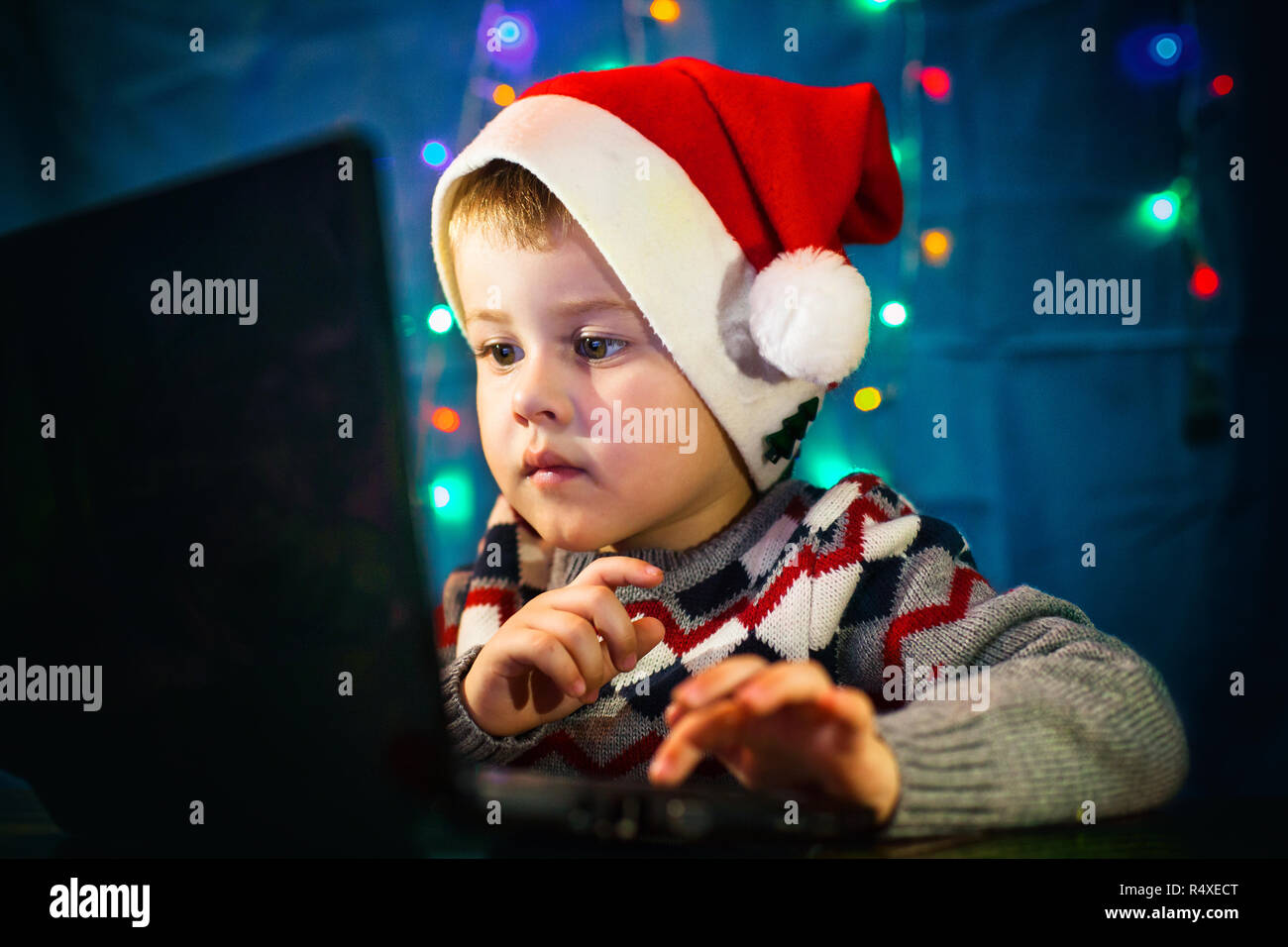 8bfc278f60d Little child writing letter to Santa Claus on laptop computer. Little boy  with santa hat