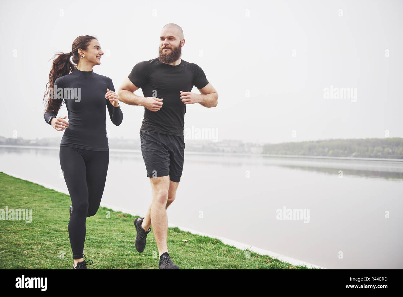 Couple jogging and running outdoors in park near the water. Young bearded man and woman exercising together in morning Stock Photo