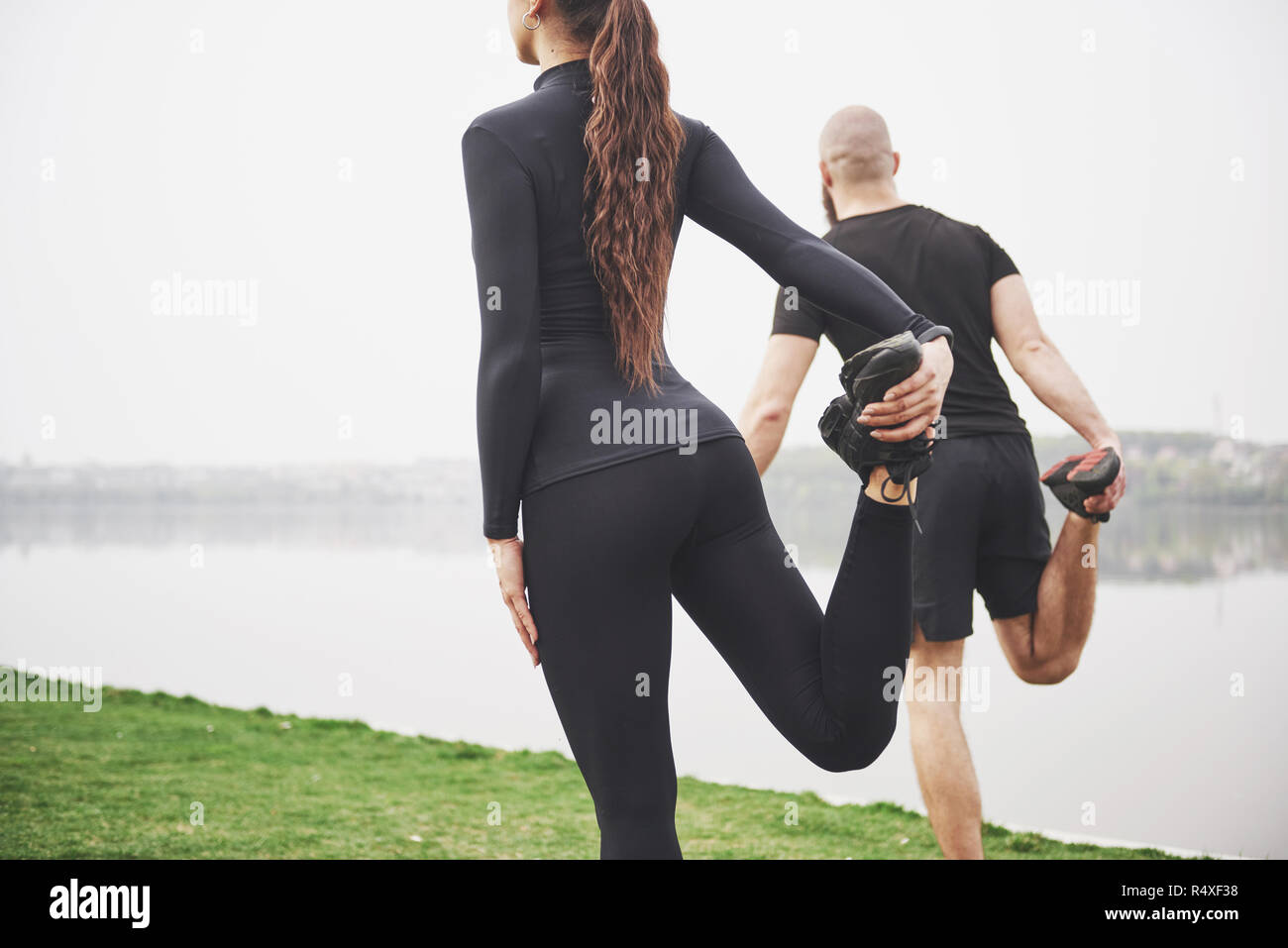 Fitness couple stretching outdoors in park near the water. Young bearded man and woman exercising together in morning Stock Photo