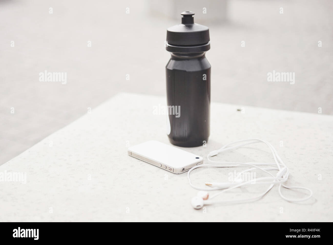 Phone headphones and a bottle of water in the open air. Accessories for running sports Stock Photo