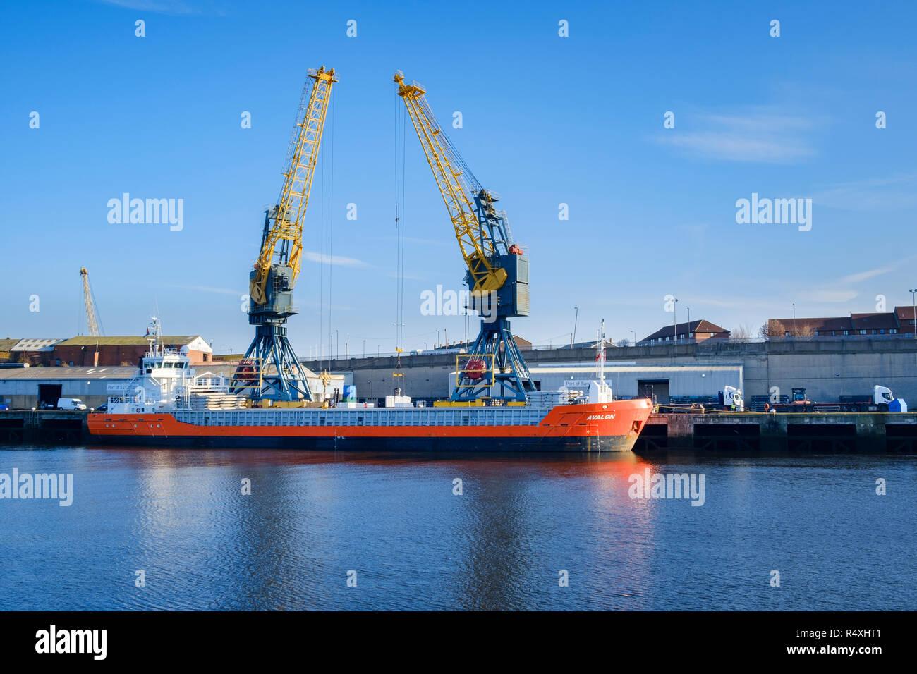 Import - Export - Port of Sunderland dock cranes on the river Wear loading cargo on general cargo ship MV Avalon merchant vessel built 2009 - Stock Image