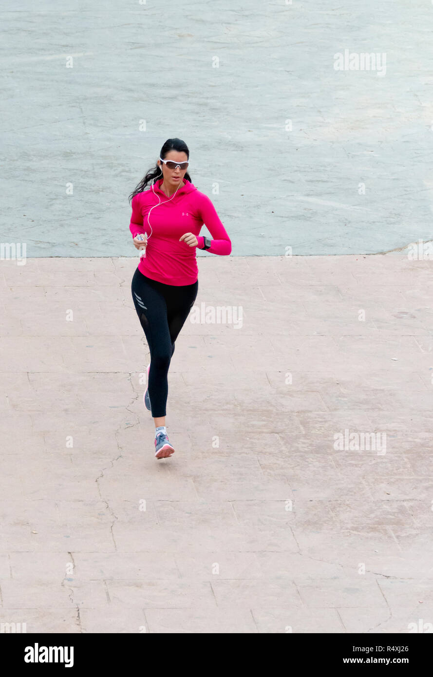 Attractive young woman in pink top and sunglasses keeping fit jogging - Stock Image