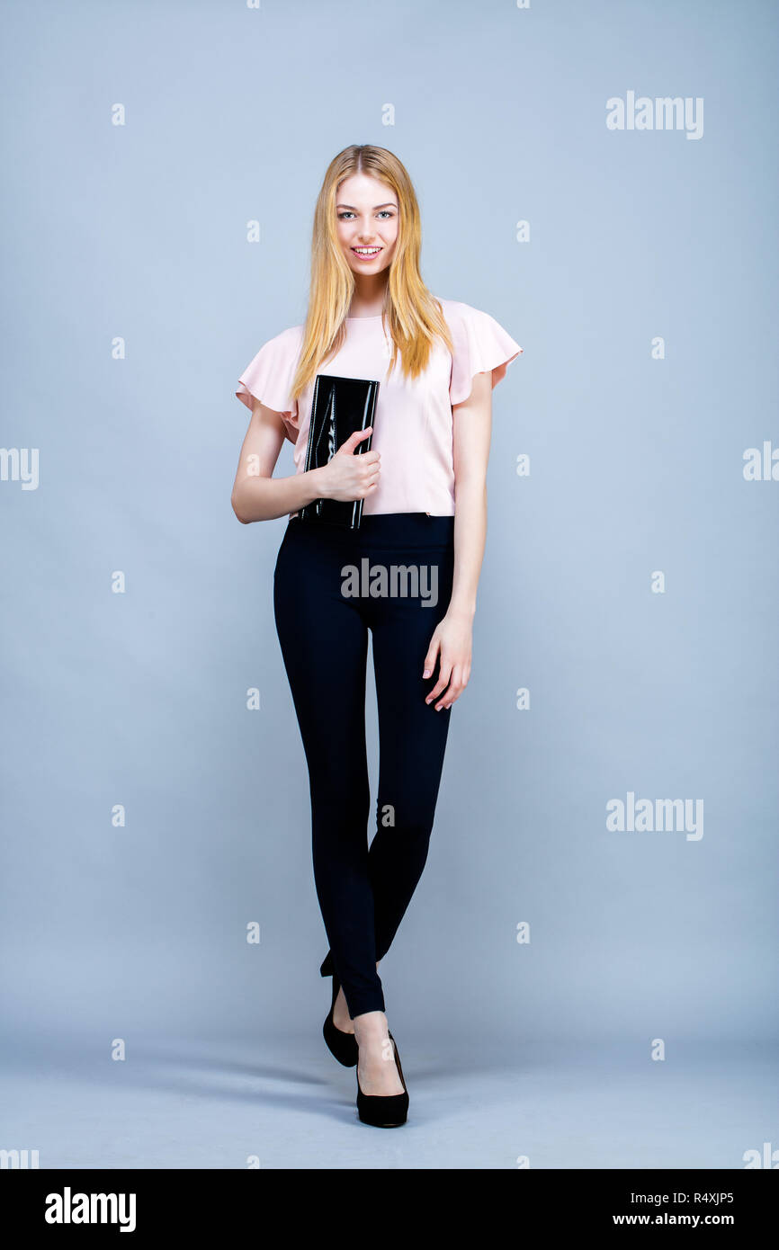 Young woman, standing, bag in hand - Stock Image