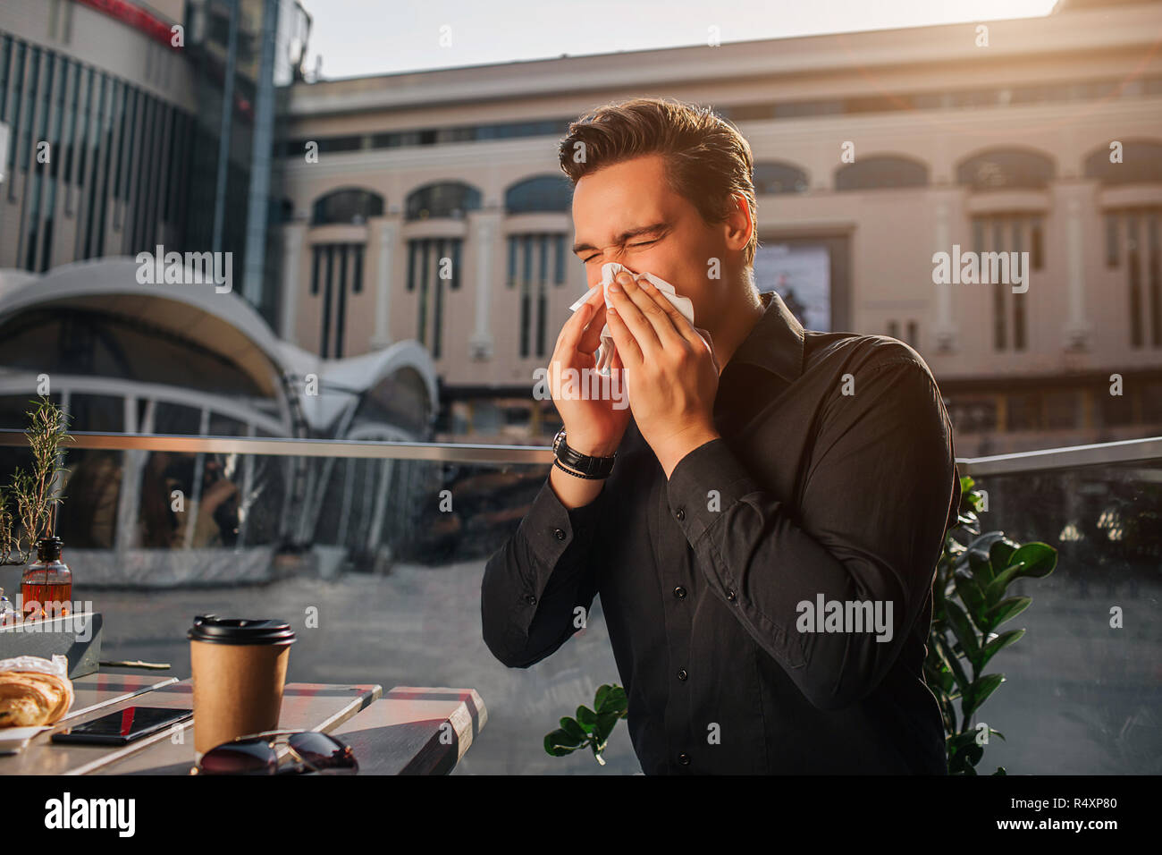 Sixk young man sit at table and sneezing in white napkin. He keeps eyes closed. Guy suffer. He sits outside. It is sunny. - Stock Image