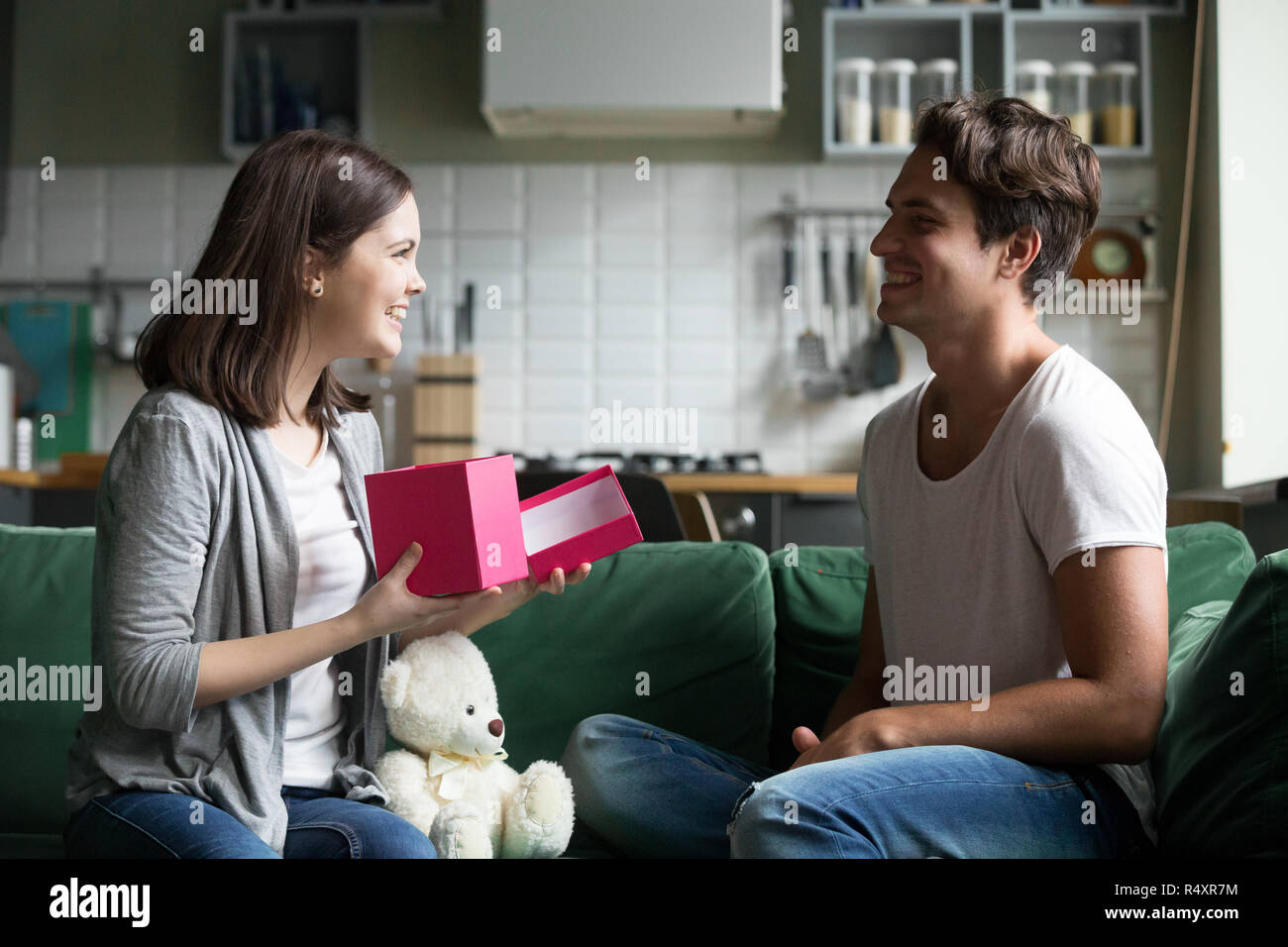 Young man gave to beloved girl a gift - Stock Image