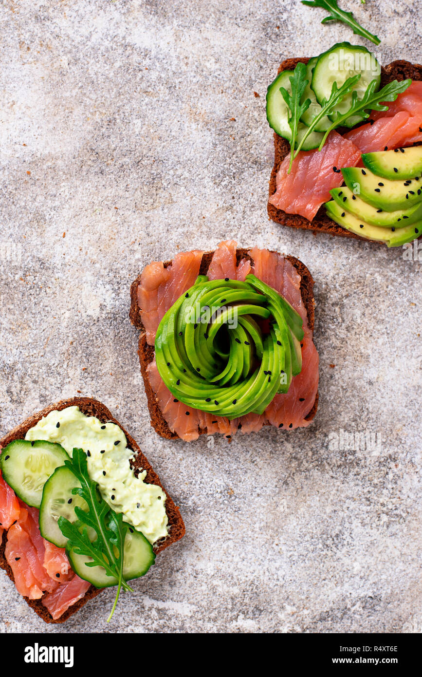Avocado toast with salmon on rye bread. Top view - Stock Image