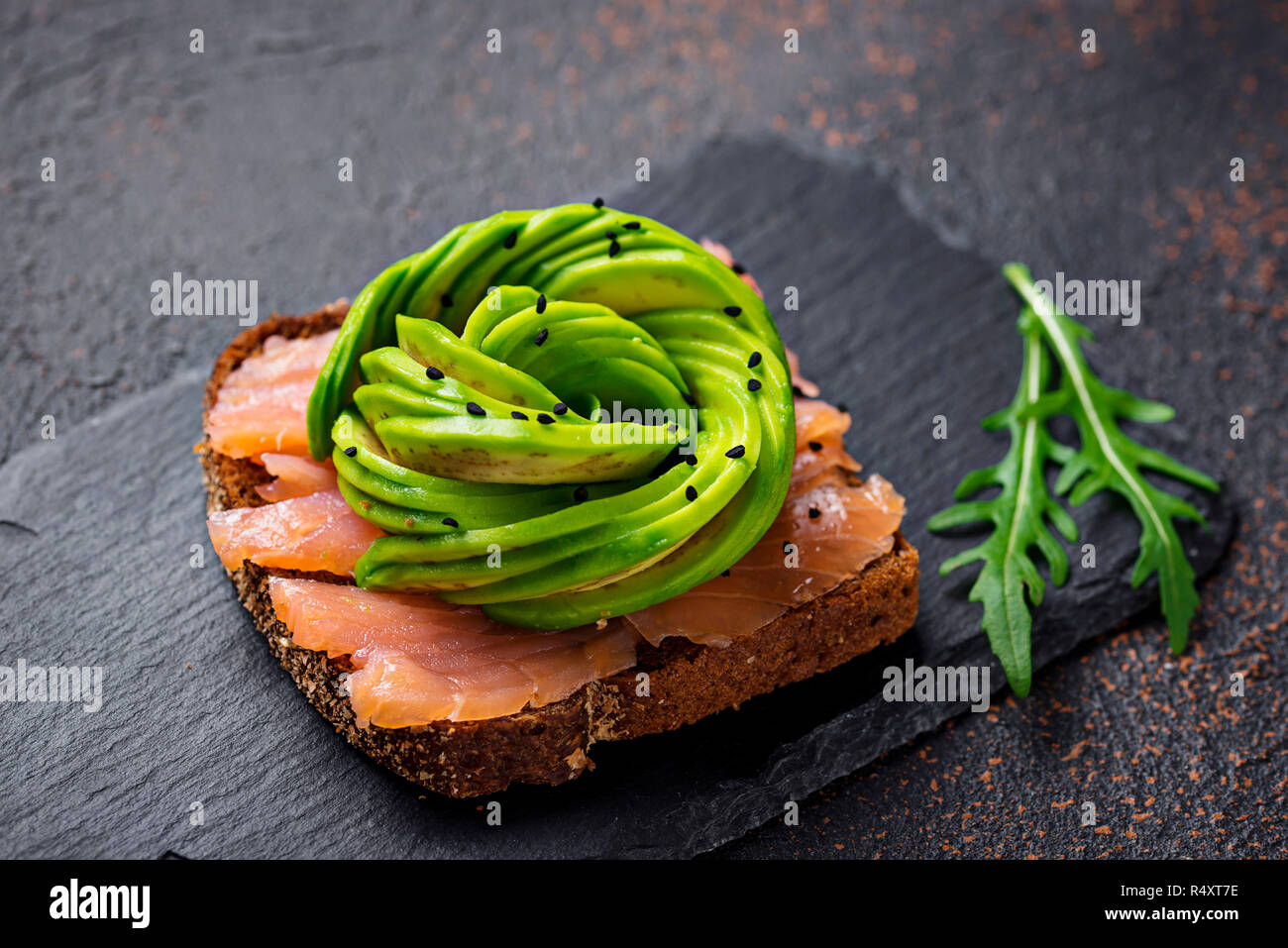 Healthy toasts with salmon and avocado rose on rue bread - Stock Image