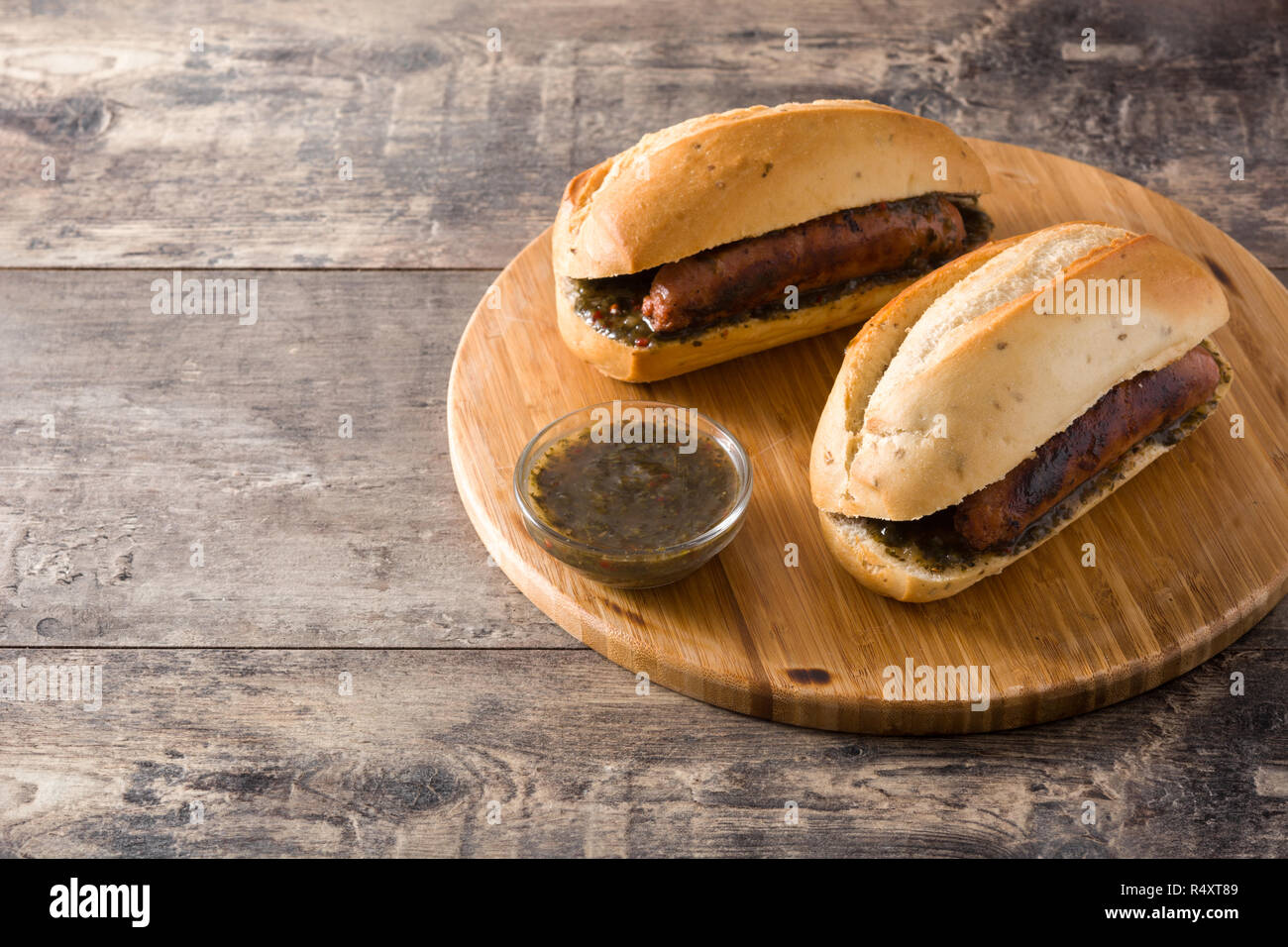 Choripan. Traditional Argentina sandwich with chorizo and chimichurri sauce on wooden table Stock Photo