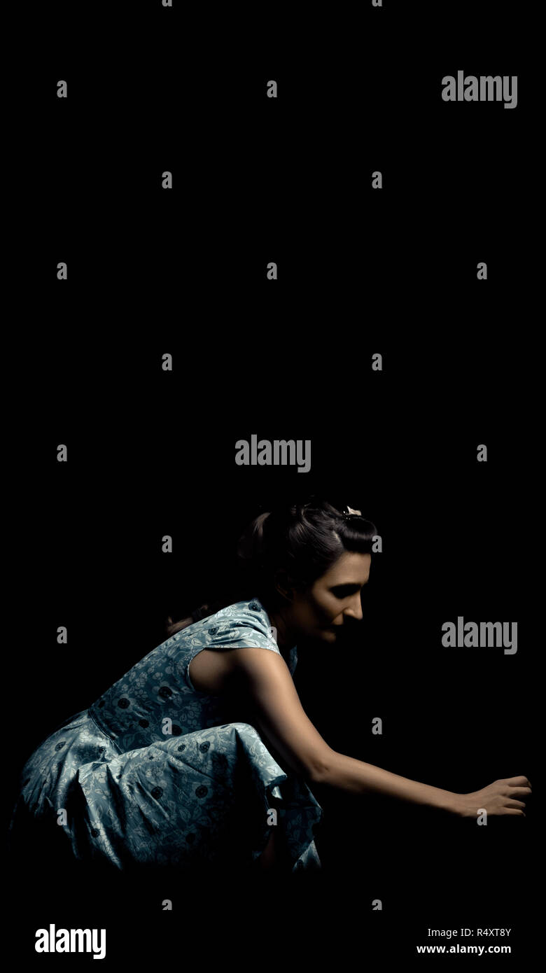 Woman crouched in a blue dress in a dark environment. - Stock Image