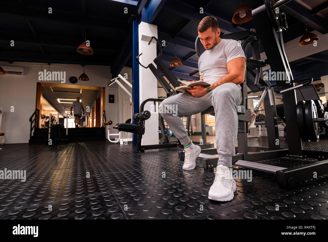 Fitness trainer writes workout plan close up in gym - Stock Image
