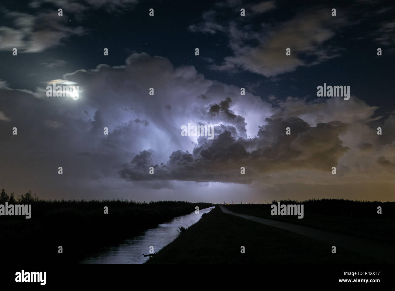 Thunderstorm clouds are illuminated by lightning. The moon is partly obscured by the storm. Location: close to the cities of Gouda and Leiden, Holland - Stock Image