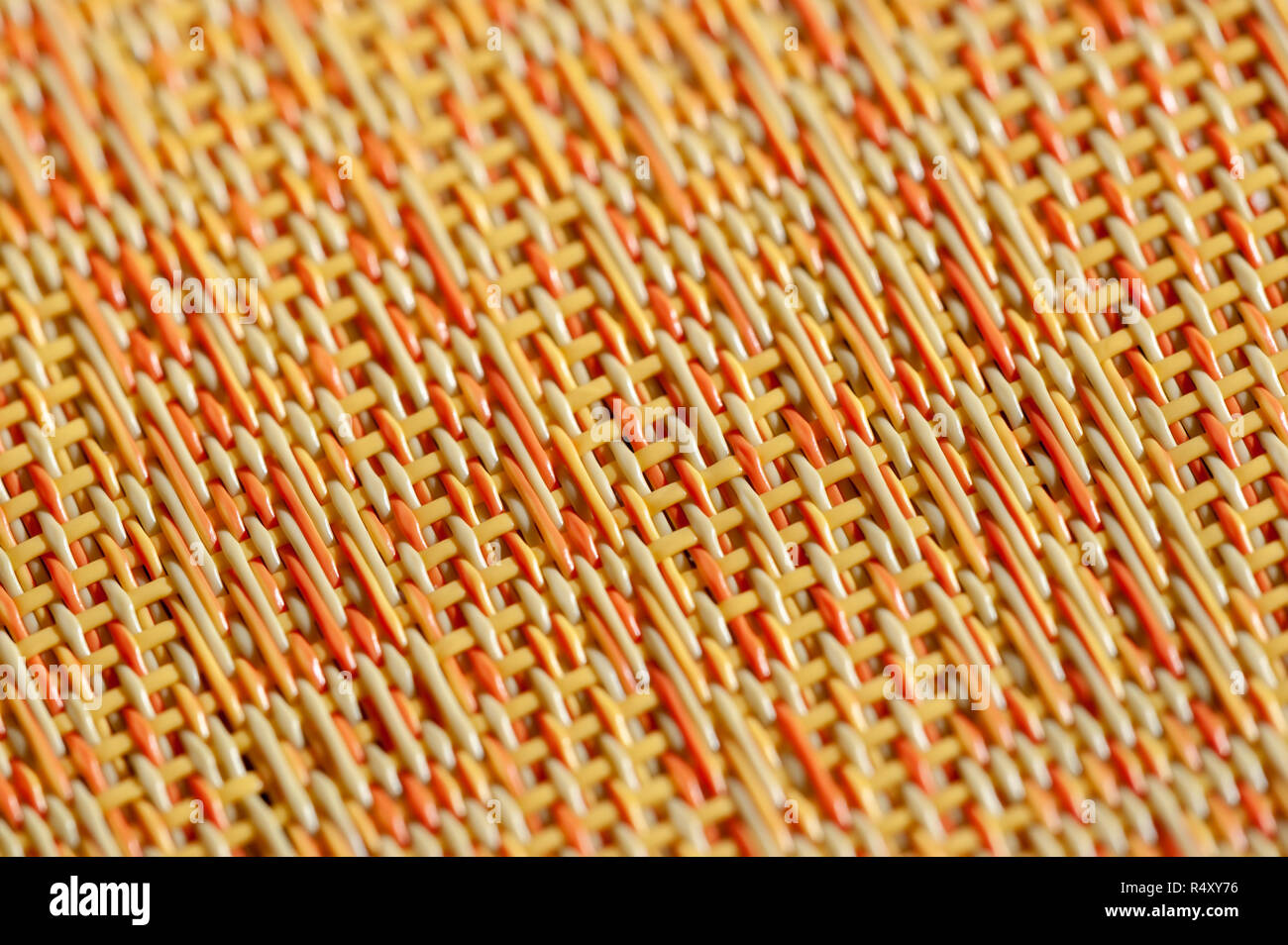 Warm colors of orange, red and yellow in an abstract woven background. - Stock Image