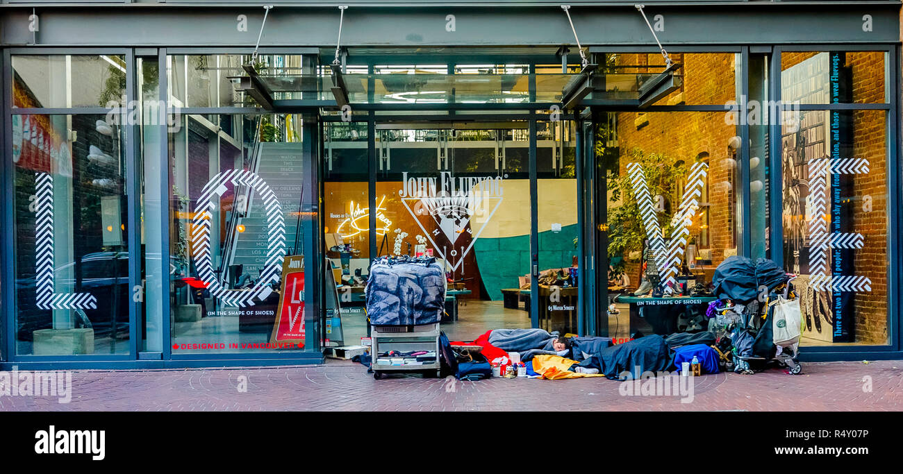Homeless person sleeps in front of Fluevog Shoes store front, Gastown, Vancouver, British Columbia, Canada - Stock Image