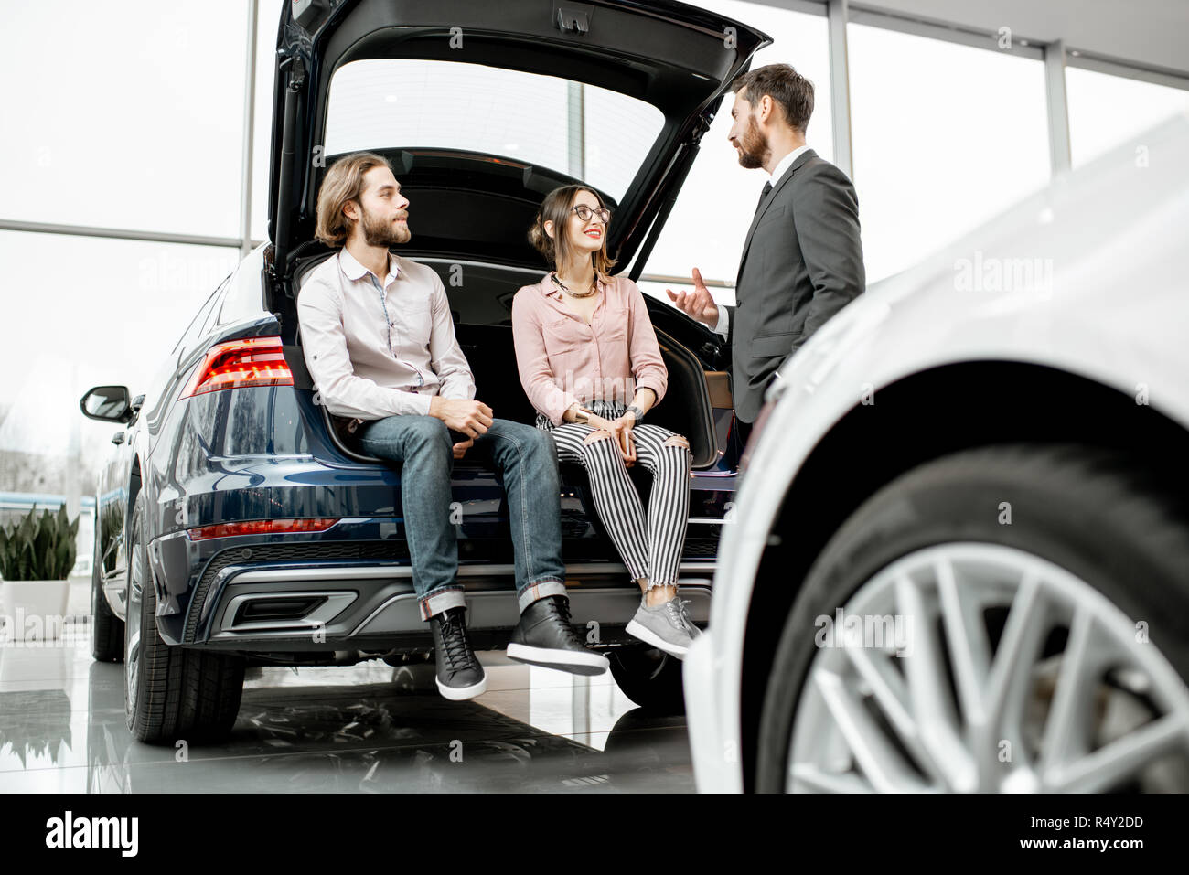 Young couple sitting in the trunk of a new car listening to the salesman at the showroom - Stock Image