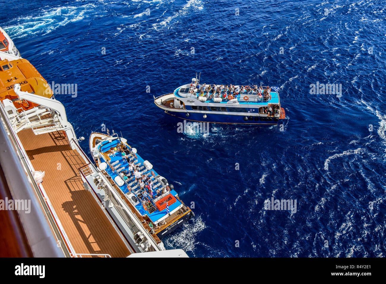 Tourists return to a cruise ship on transport tender boats inside the Santorini island caldera on the Aegean Sea. - Stock Image