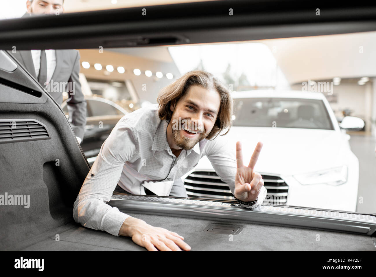 Funny portrait of a young man looking in the trunk of a new car in the showroom - Stock Image