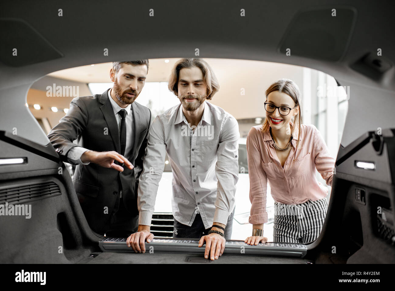 Salesman showing spacious trunk of a new car for a young couple clients in the showroom - Stock Image