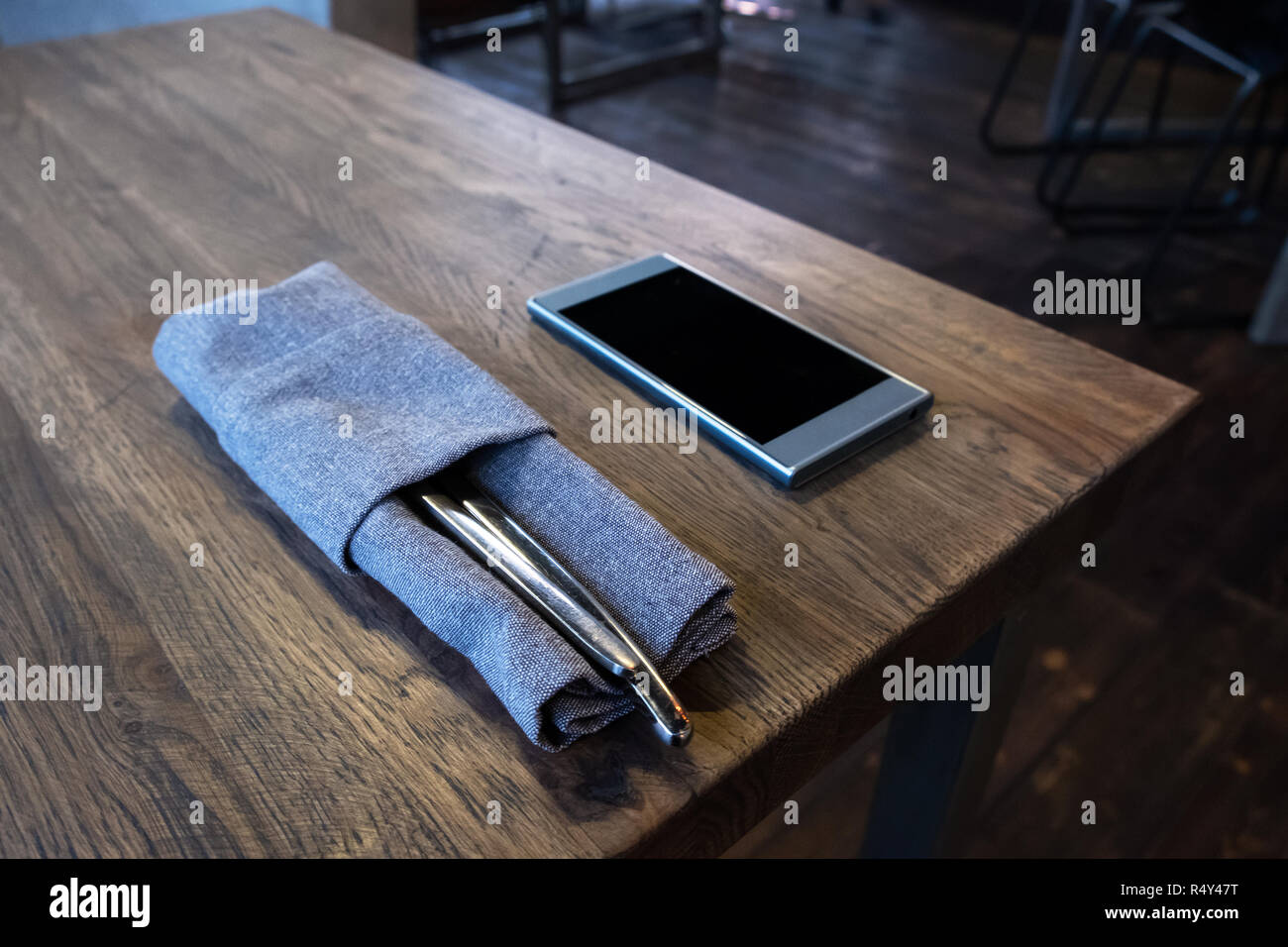 Mobile phone with cutlery set on wooden table in restaurant. Smartphone addiction concept. Ordering food online - Stock Image