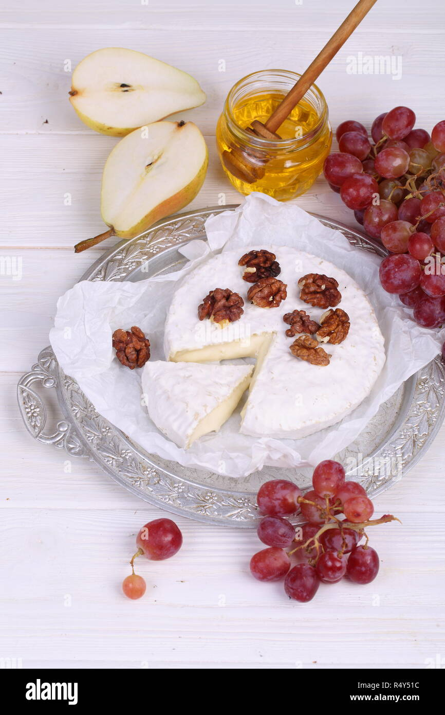 Camembert with honey, pear and grapes - Stock Image