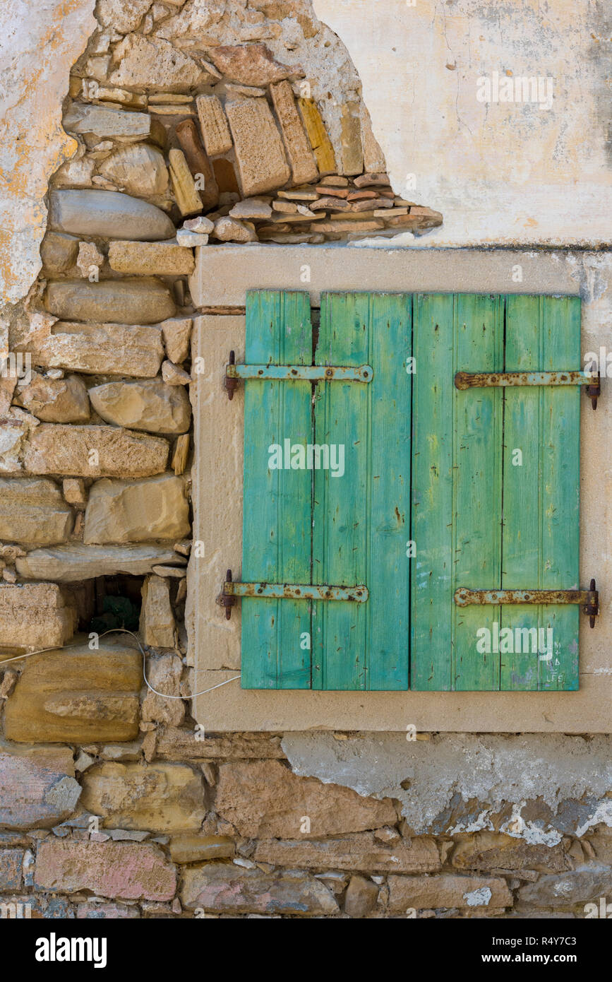 an old and derelict wall with a green painted shabby chic style wooden shutter. rustic window with peeling paint on traditional wooden shutters. - Stock Image