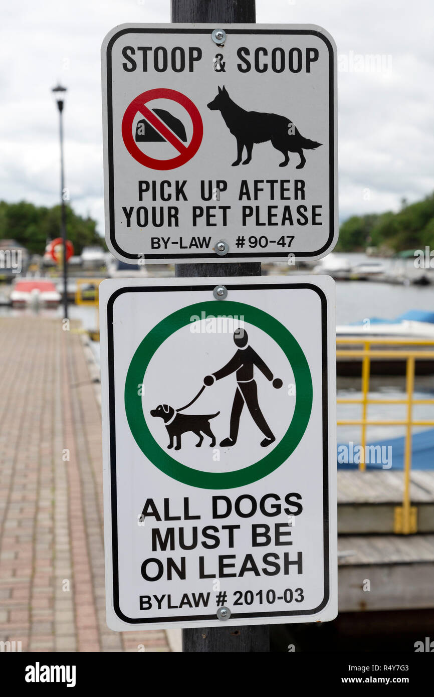 Signs remind pet owners to pick up after their pets at Gananoque in Ontario, Canada. The signs also tell owners to keep their dogs on a leash. - Stock Image