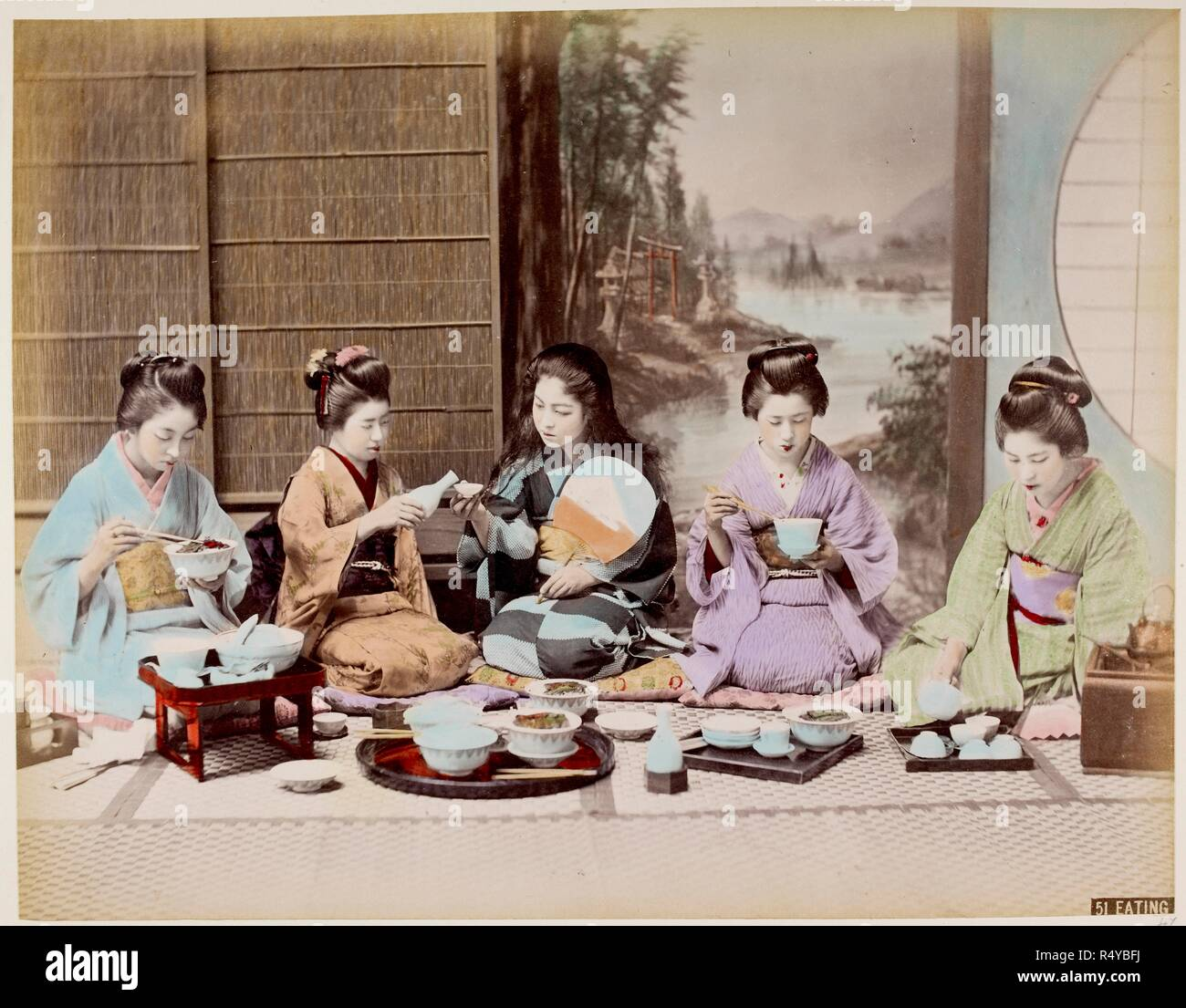 A group of Japanese women eating a meal in a traditional house. Wearing formal traditional costumes of kimono and obi with decorated dressed hair. Sitting on the floor. . Scenes from life in Japan. Circa 1880s Hand-coloured albumen print. Source: Photo 752/24 47. - Stock Image
