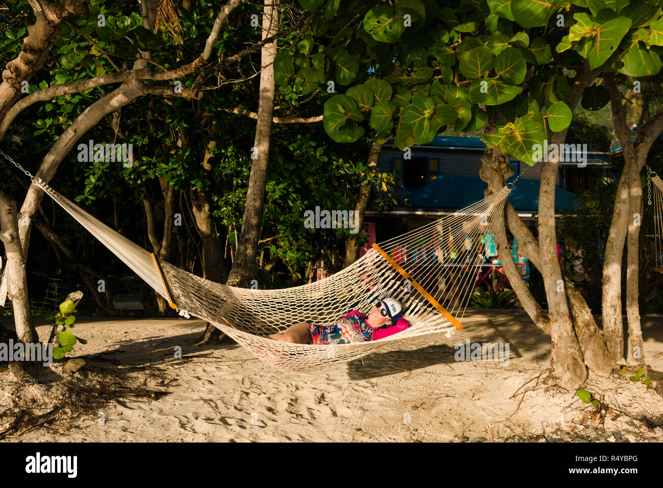 A woman relaxes in a hammock on Belle Vue village on Jost Van Dyke island in the British Virgin Islands bareboat yacht charter vacation. - Stock Image