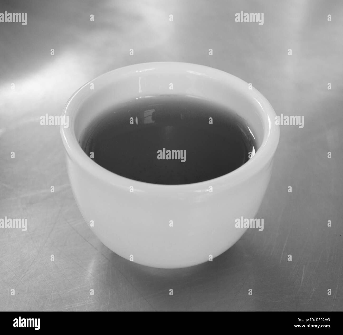 CUP OF CHINESE GREEN TEA ON STEEL TABLE - Stock Image