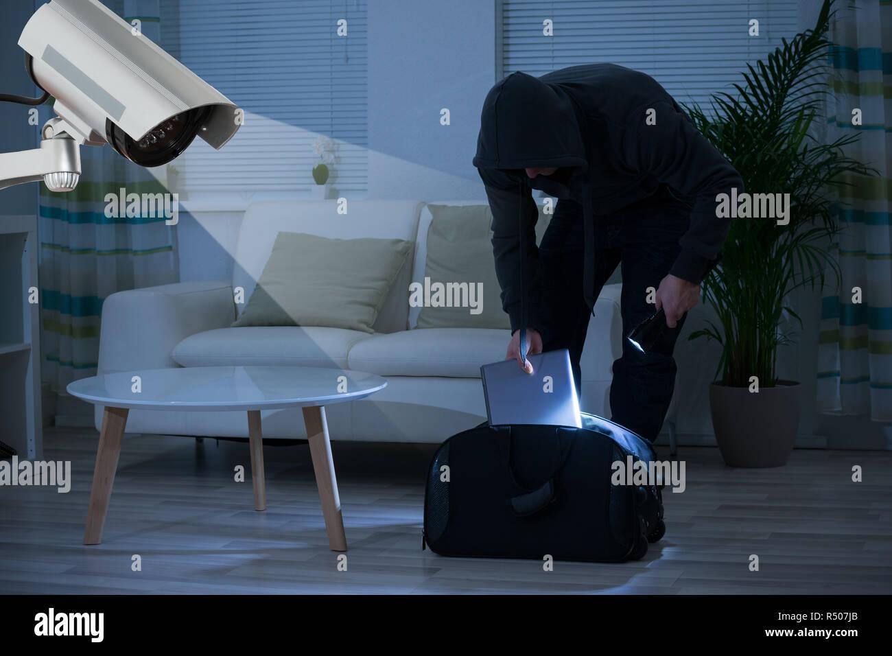 Burglar Putting Laptop Into Bag At Home - Stock Image