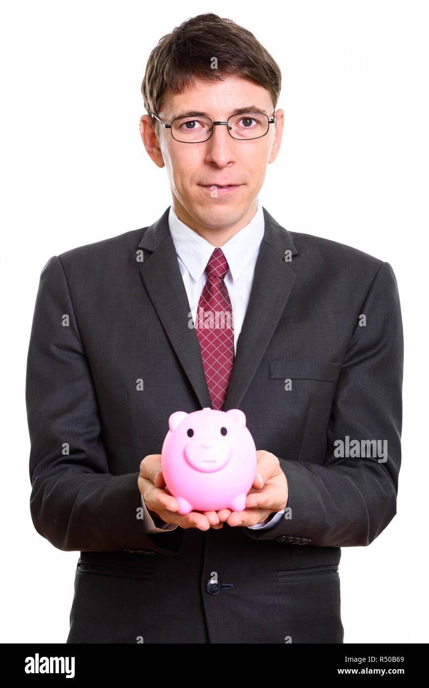 Studio shot of businessman holding piggy bank - Stock Image