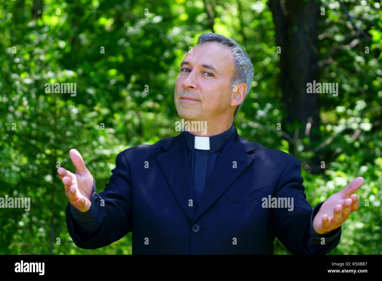 A good looking catholic priest is walking in the forest. Standing and looking at us with confidence, openning his arms. - Stock Image
