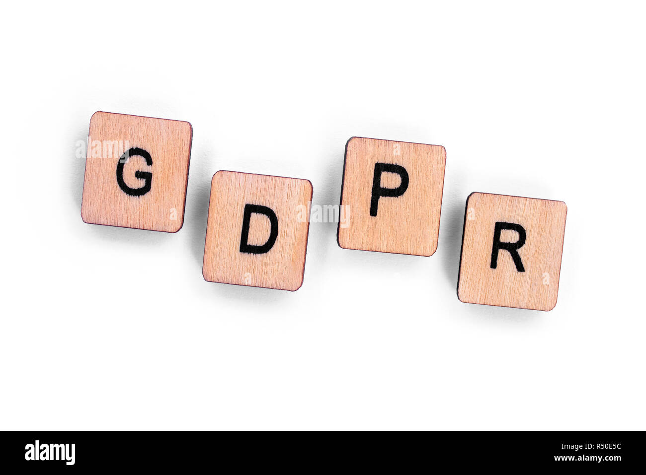 The abbreviation GDPR - General Data Protection Regulation, spelt with wooden letter tiles over a plain white background. Stock Photo