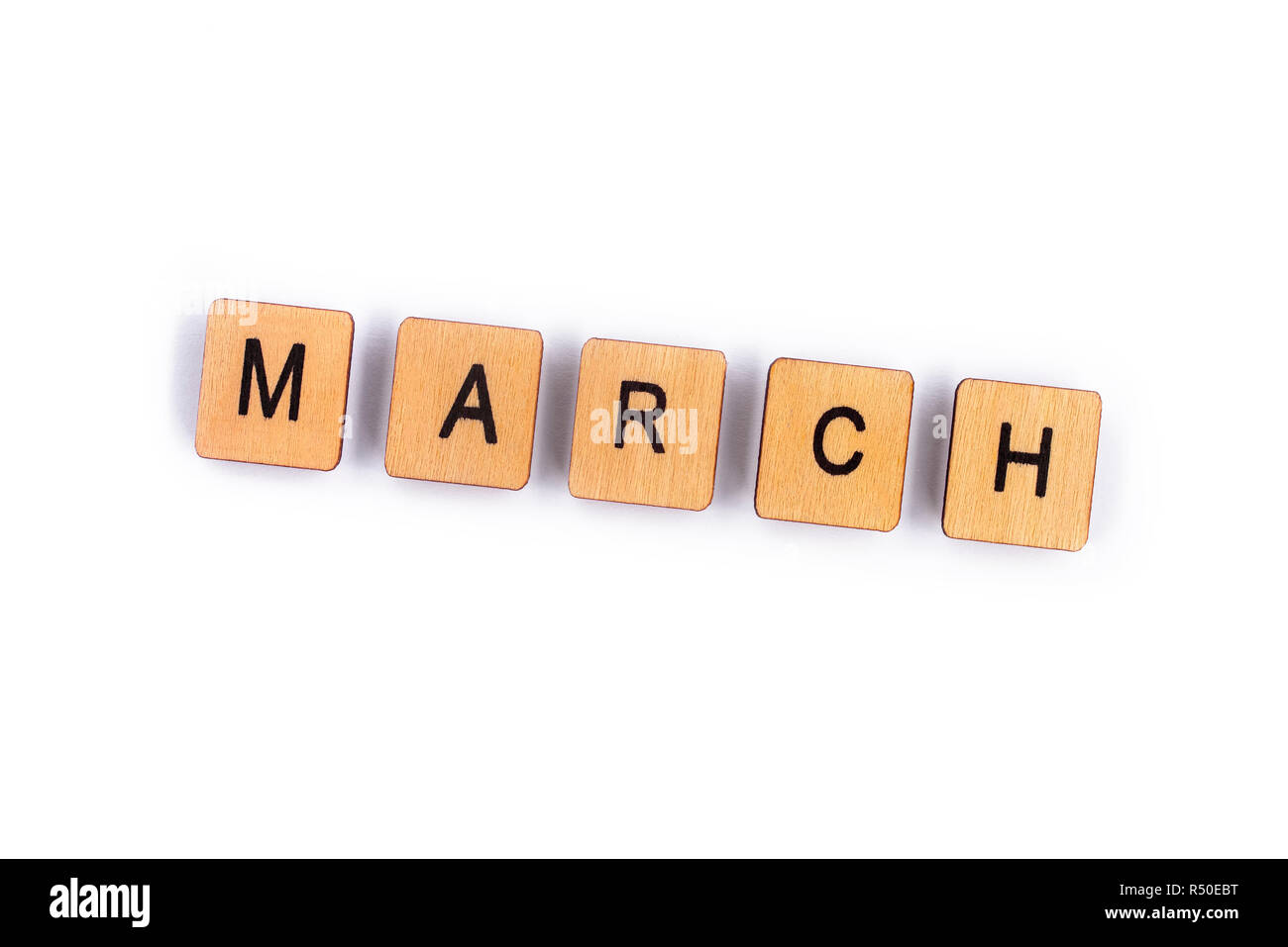 March Spelt With Wooden Letter Tiles Over A Plain White