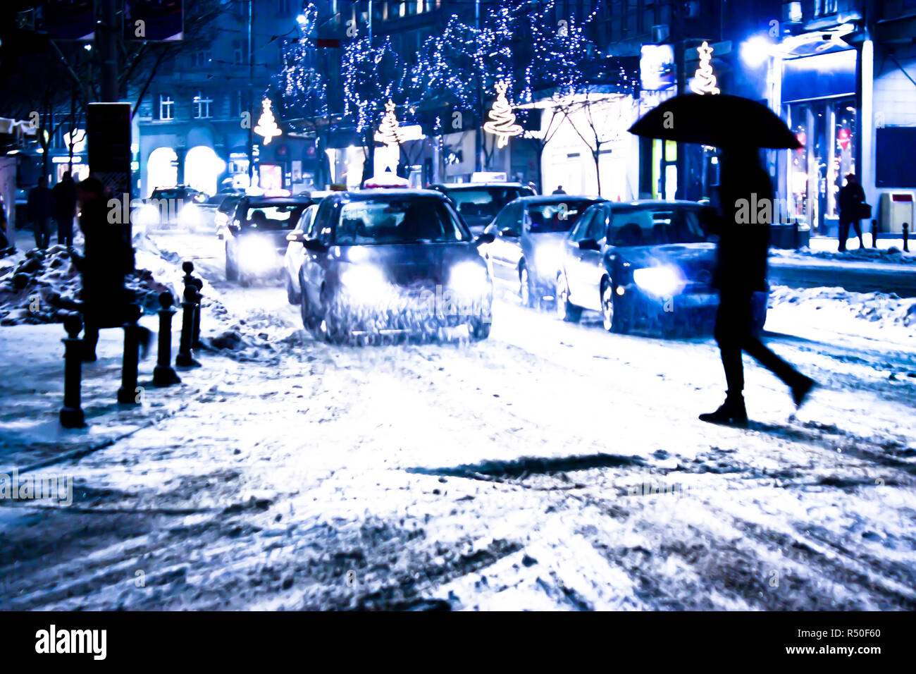 Blurry snowy city night traffic with pedestrian silhouete crossing the street - Stock Image