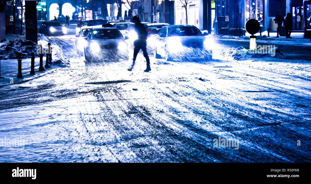 Blurry snowy city night traffic with pedestrian silhouete crossing the sreet - Stock Image