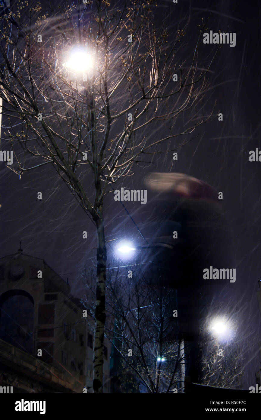 Blurry person walking alone in snowy and windy city streets in winter night , low angle view - Stock Image