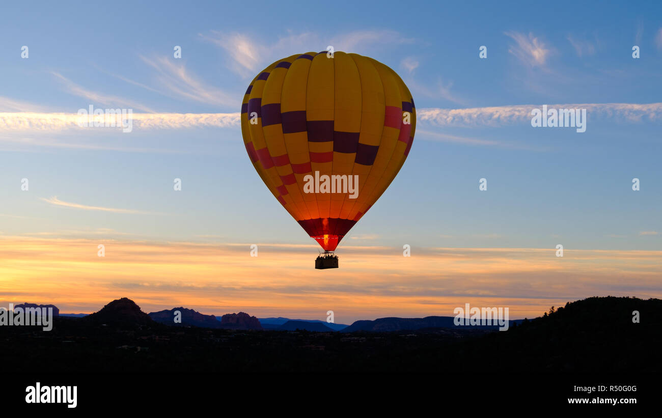 Bright yellow hot air balloon flying over desert mountains at dawn - Stock Image