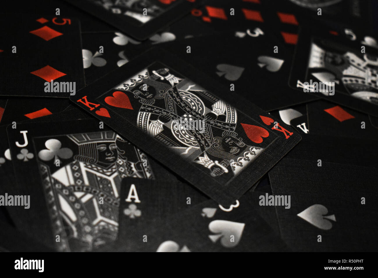 Stunning shot of black and white playing cards, with the King of Hearts resting atop the pile. Hints of red add emphasis to the heart symbol. - Stock Image