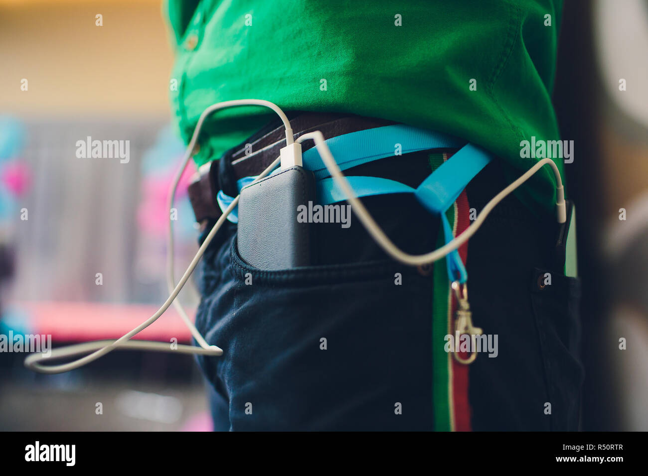 power bank lies in a back pocket of jeans, in the other is a mobile phone that is charged. Stock Photo