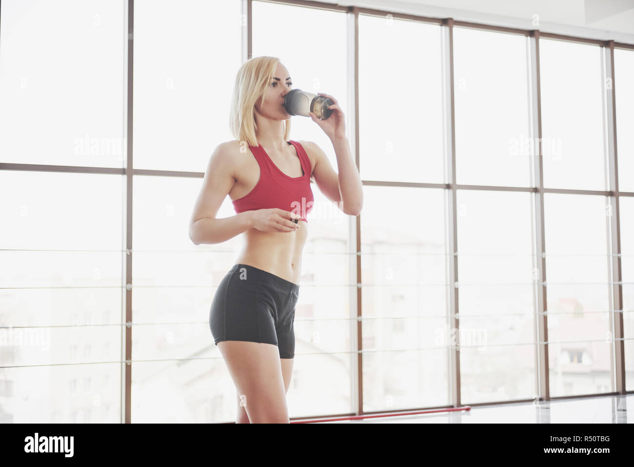 Photo of attractive fitness woman in gym holding bottle of water Stock Photo