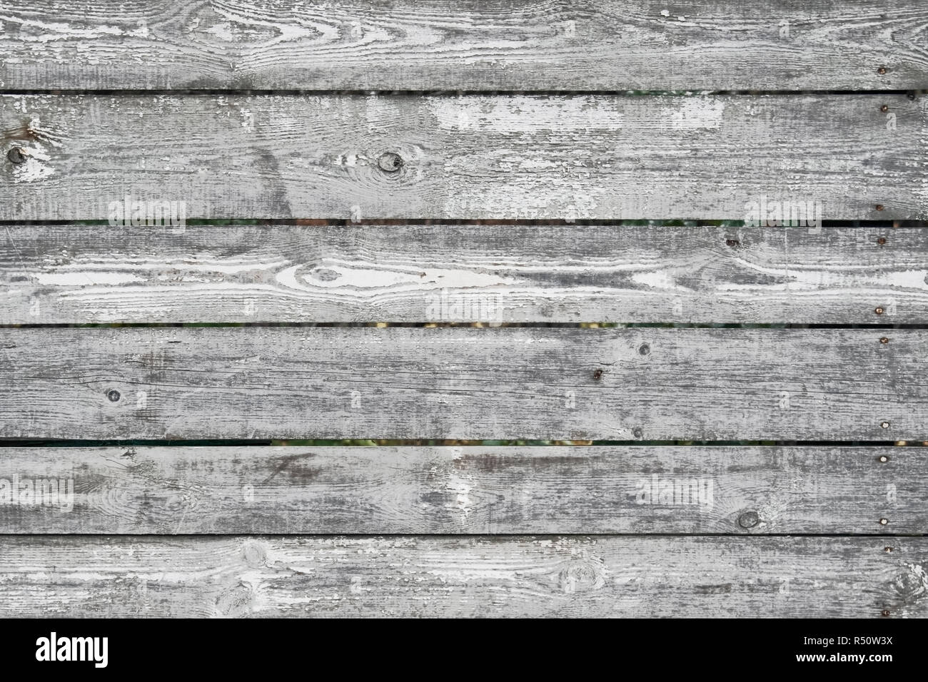 Fence wooden gray with the peeled-off white paint texture of a tree - Stock Image