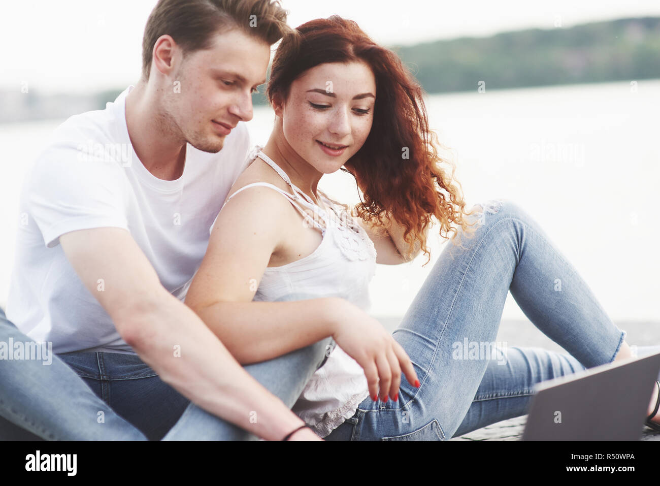 Young couple in the summer for a laptop in the park. Stock Photo