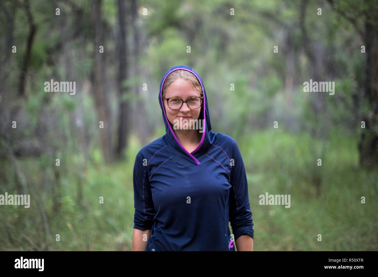 Front view waist up portrait of female raft guide in blue hooded sweatshirt and eyeglasses in forest - Stock Image
