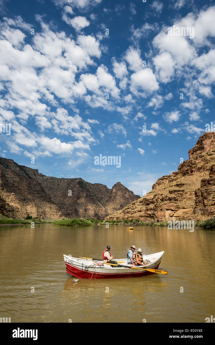 View of three adventurous people in rowboat on Desolation/Gray Canyon section, Green River, Utah, USA - Stock Image