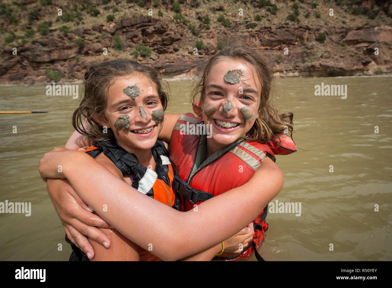 Two children playing in the river and painting mud on each others faces while on a Green river rafting trip, Desolation/Gray Canyon section, Utah, USA - Stock Image