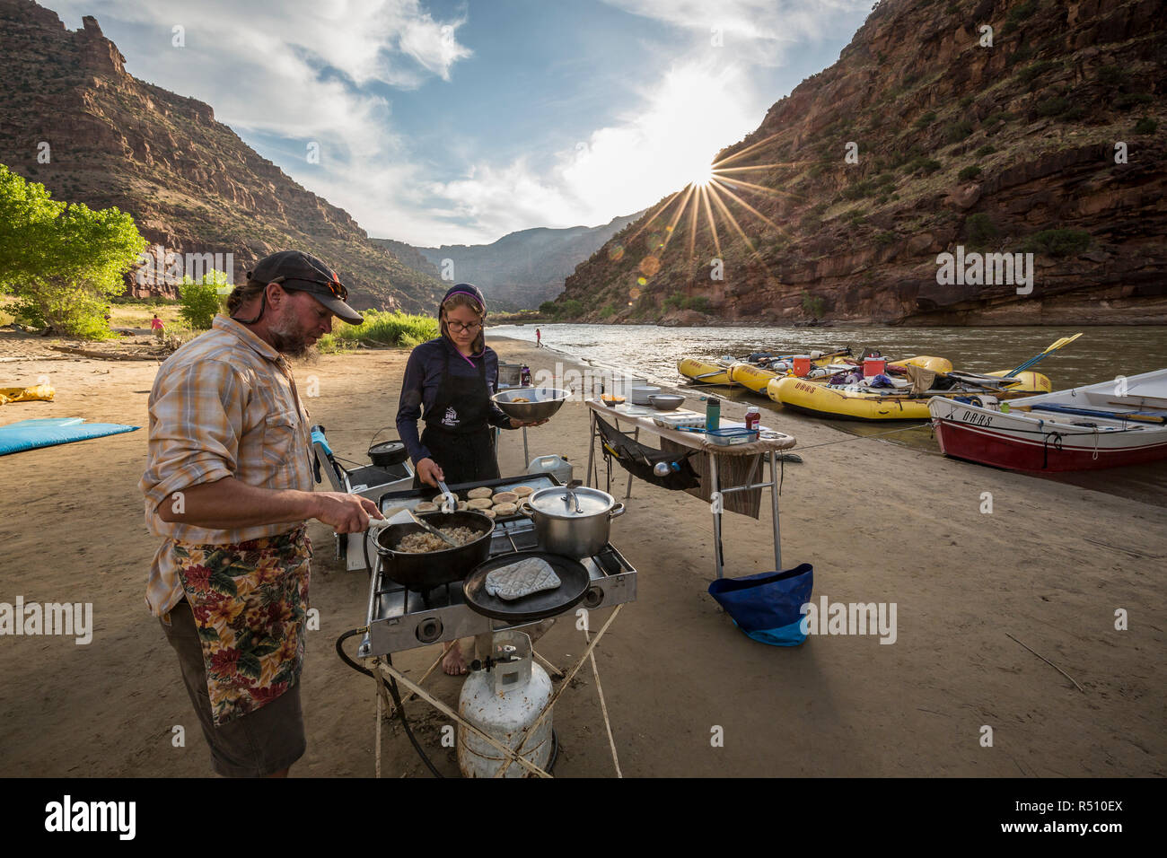 Two rafting guides cooking a meal at camp while on a Green river rafting trip, Desolation/Gray Canyon section, Utah, USA - Stock Image