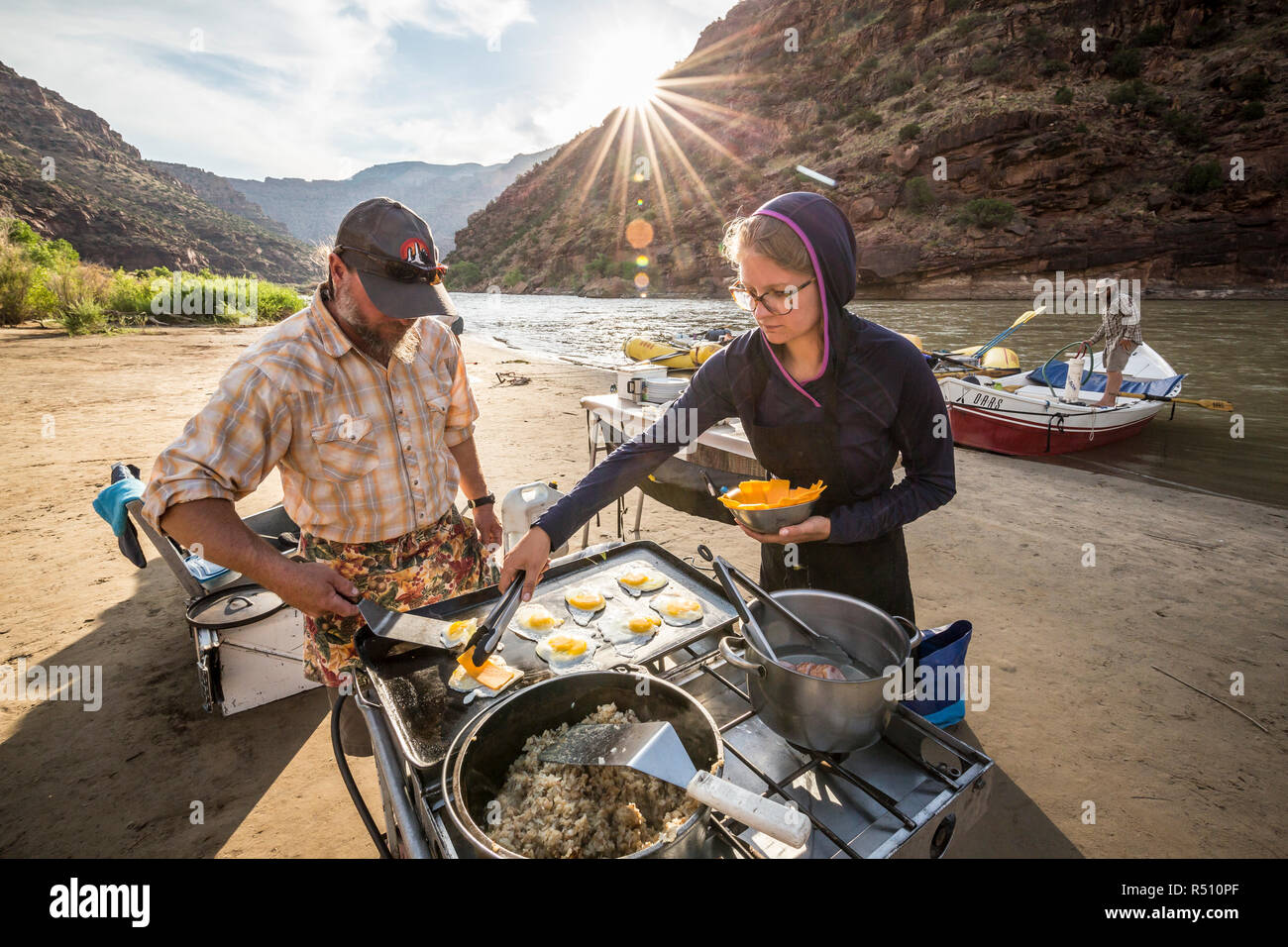 Two rafting guides cooking a meal at camp while on a Green river rafting trip, Desolation/GrayCanyon section, Utah, USA - Stock Image