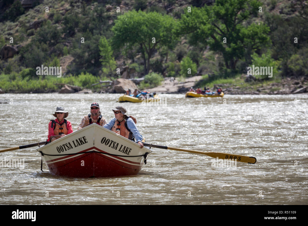 Two women and man paddling in Dory rowboat on Desolation. Gray Canyon section of Green River, Utah, USA - Stock Image