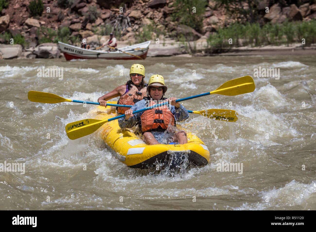 A man and woman paddling aninflatablekayak through rapids on a Green river rafting trip, Desolation/GrayCanyon section, Utah, USA - Stock Image