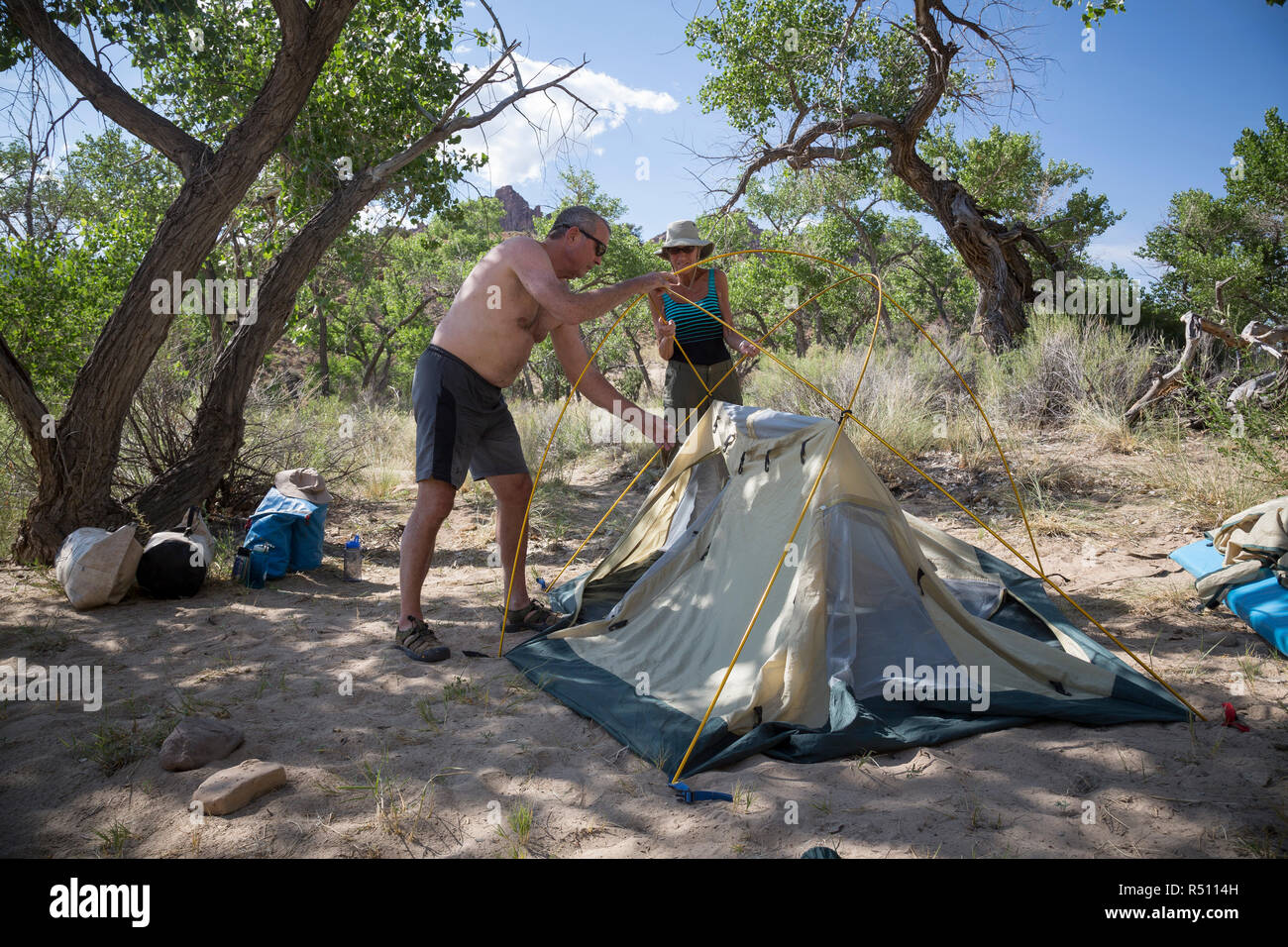 A man and woman setting up a tent at camp during a Green river rafting trip, Desolation/Gray Canyon section, Utah, USA - Stock Image